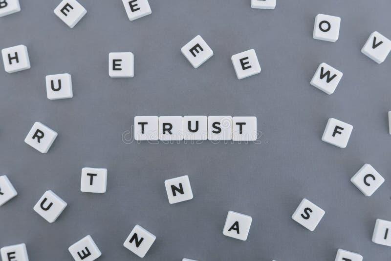 Förtroendeord som göras av fyrkantigt bokstavsord på grå bakgrund royaltyfria foton