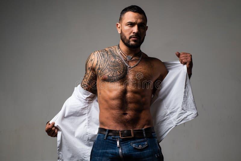 Förtroendeutstrålning muskul?s macho man med den idrotts- kroppen sport och kondition, hälsa sexig abs av tatueringmannen manlig royaltyfria foton