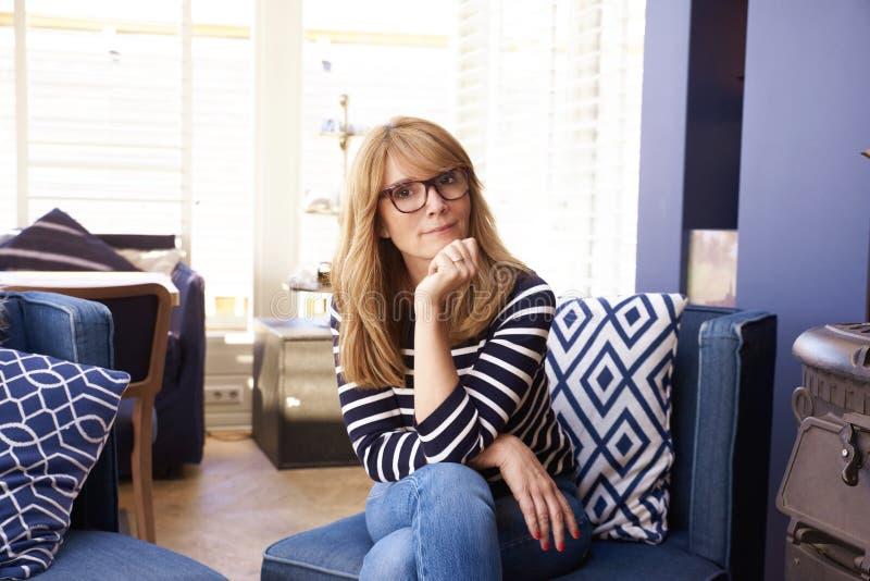 Förtrolig leende kvinna som lättar pÃ¥ soffan hemma fotografering för bildbyråer