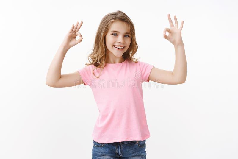 Förtroliga, trevliga, smarta, små flickor försäkrar allt okej, ler sig nöjda, godkänner en cool onlinekurs, att döma arkivfoto