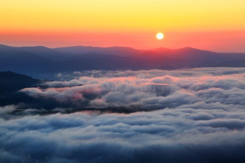 Förtrollande soluppgång på de höga bergen och längst ner där är texturerad tjock dimma arkivbild