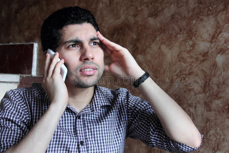 Förtvivlan av den arabiska egyptiska affärsmannen som talar med telefonen royaltyfria foton