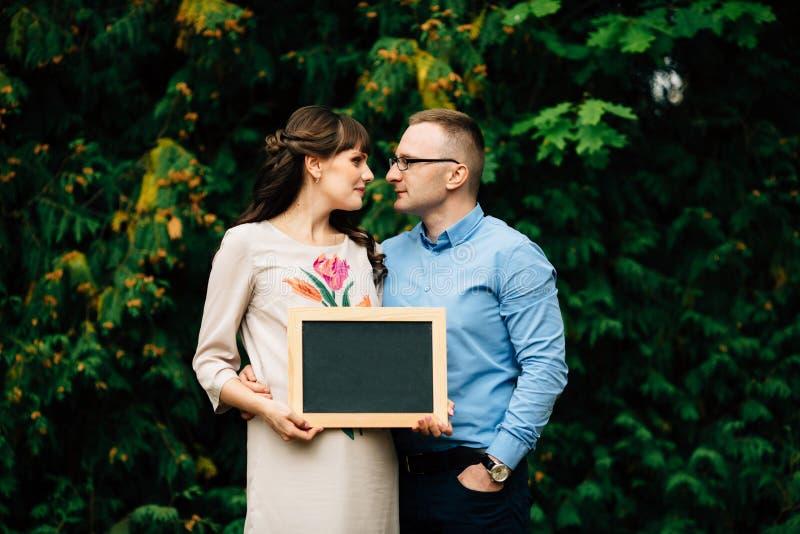 Förvänta gravida lyckliga stilfulla par som rymmer ett tomt kol, stiga ombord royaltyfria foton
