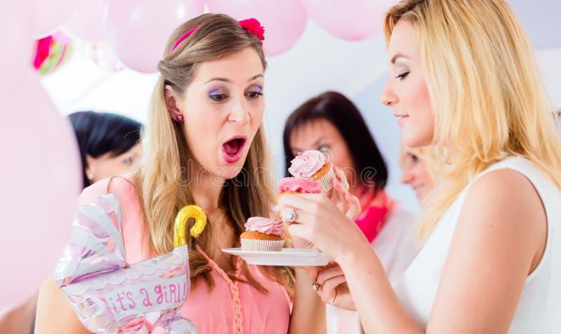 Förvänta modern som äter muffin på baby showerpartiet royaltyfri bild