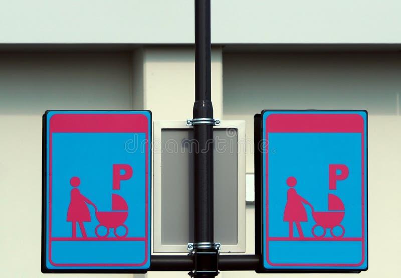 Förväntansfulla mödrar med behandla som ett barn parkeringstecknet Rosa färgen och blått undertecknar med den gravida mamman och  arkivfoton