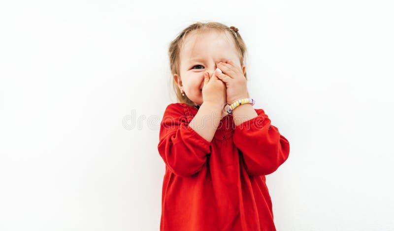 Förväxlade sinnesrörelser av lilla flickan klädde den röda blusen på den vita bakgrunden arkivbilder