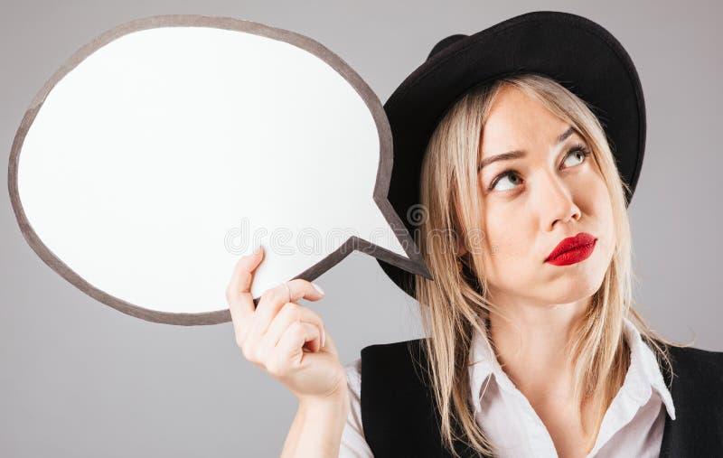 Förväxlande fundersam woamn i hattinnehav förbigår baneranförande som är buble för din text arkivbild