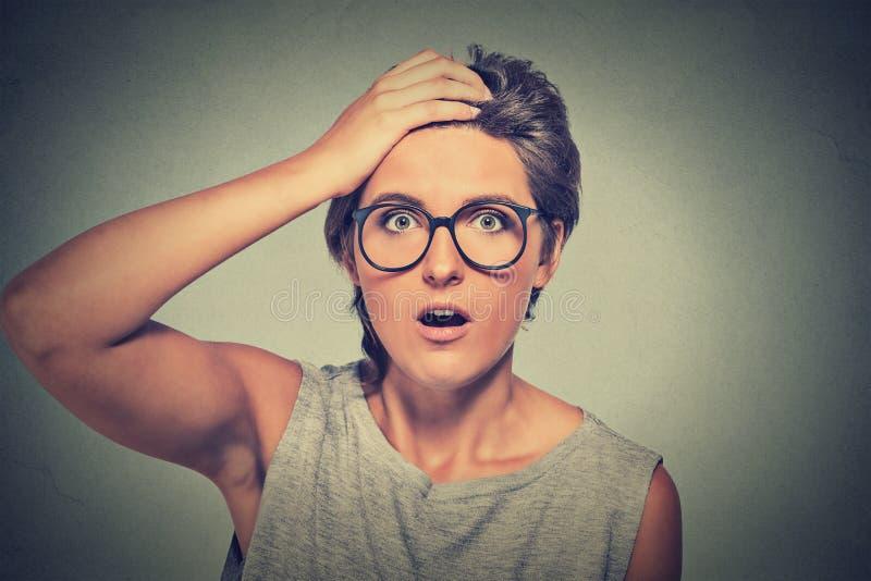 Förvåna den förvånade kvinnan med exponeringsglas som ser oavkortad misstro royaltyfri bild