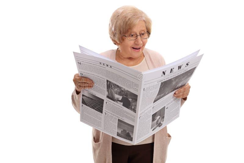 Förvånad äldre kvinna som läser en tidning royaltyfri bild