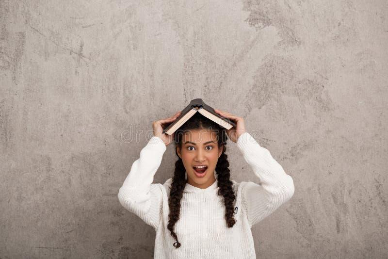 Förvånad afrikansk flickainnehavbok ovanför huvudet över beige bakgrund royaltyfria foton