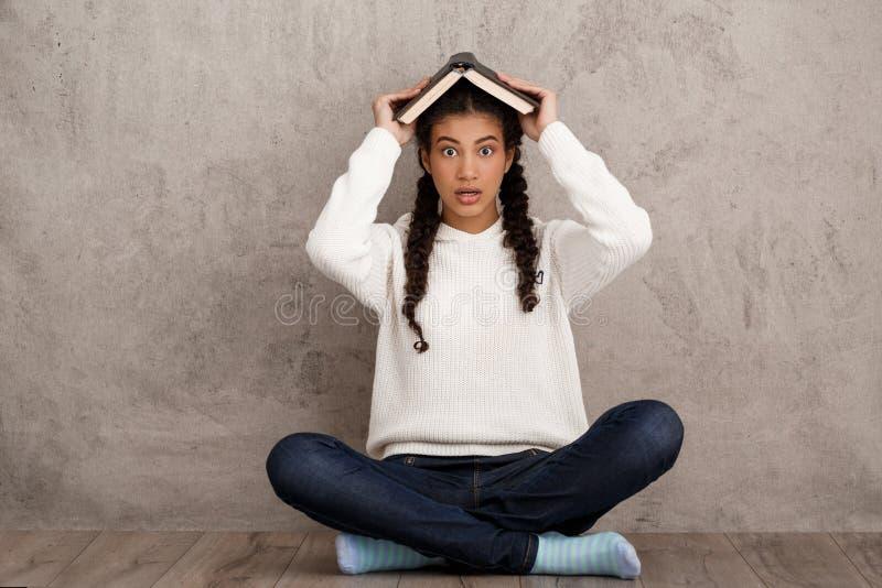 Förvånad afrikansk flickainnehavbok ovanför huvudet över beige bakgrund arkivfoto