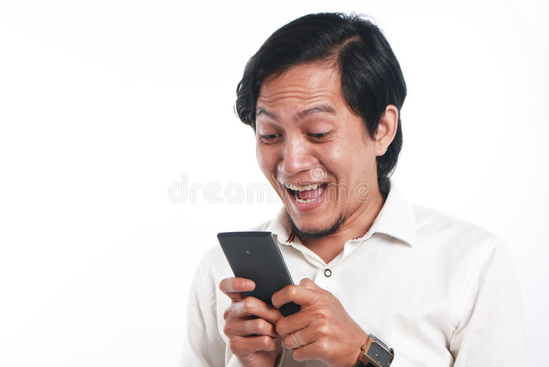 Förvånad asiatisk man med hans smarta telefon fotografering för bildbyråer