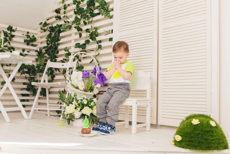 Förvånad barnpojke med styckfödelsedagkakan royaltyfri fotografi