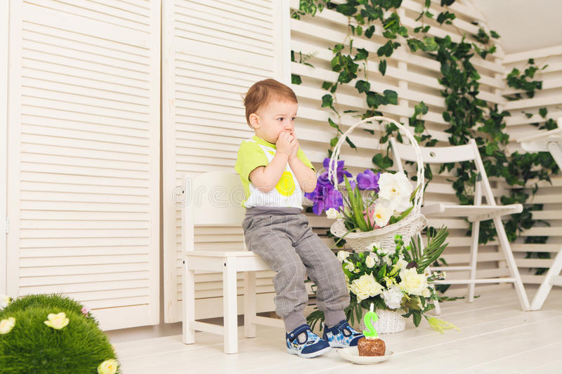 Förvånad barnpojke med styckfödelsedagkakan arkivfoto