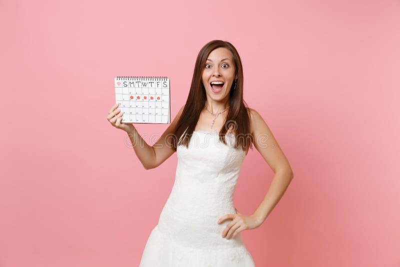 Förvånad brudkvinna i den vita bröllopsklänningen som rymmer den kvinnliga periodkalendern för att kontrollera på menstruationdag arkivbilder