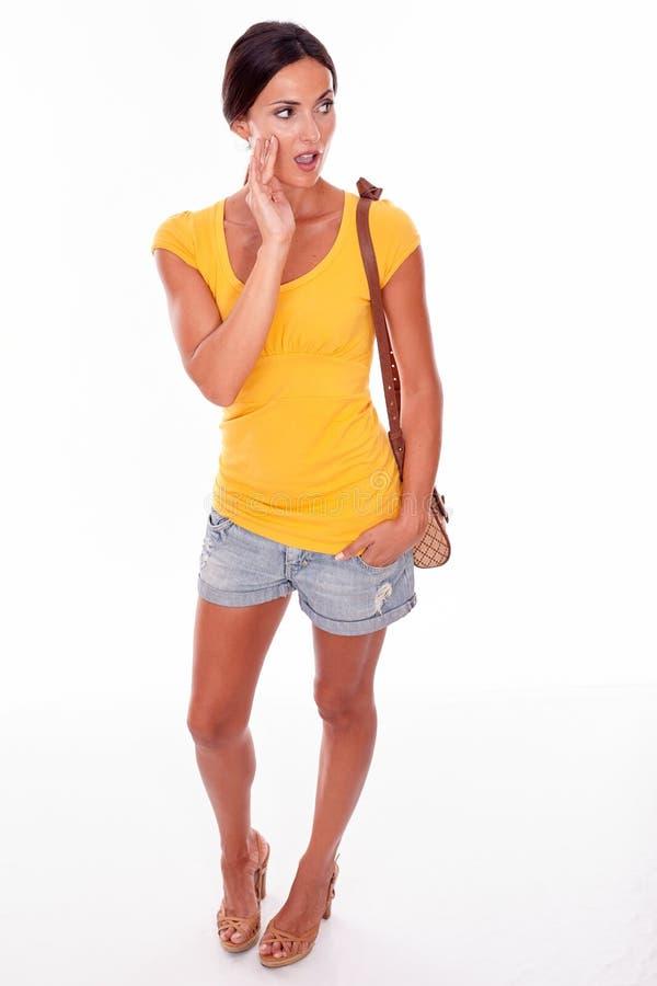 Förvånad brunettkvinna med den bruna handväskan royaltyfri bild