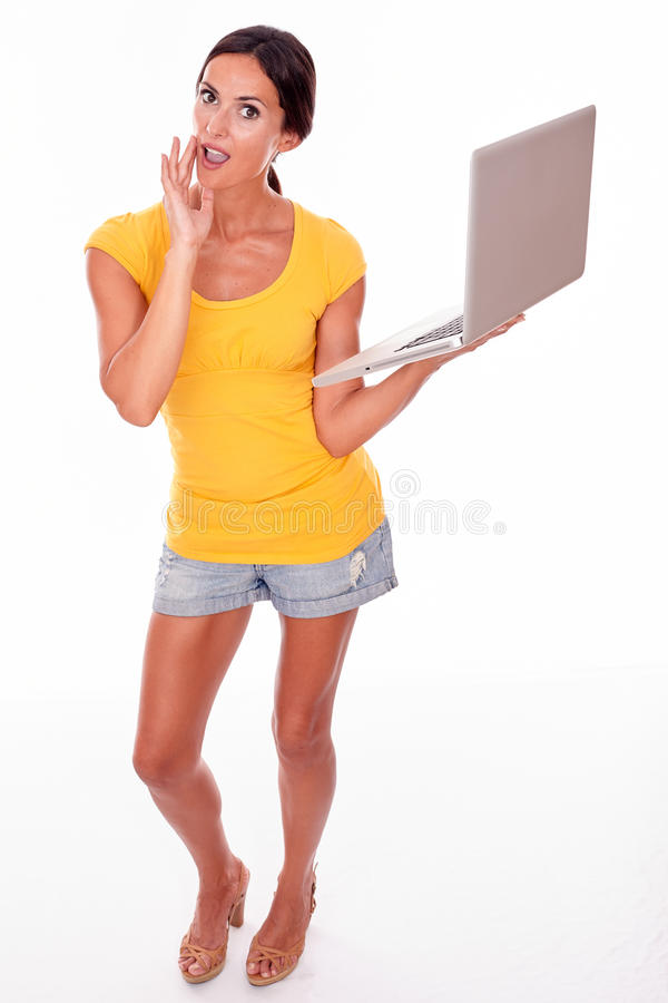 Förvånad brunettkvinna med en bärbar dator fotografering för bildbyråer