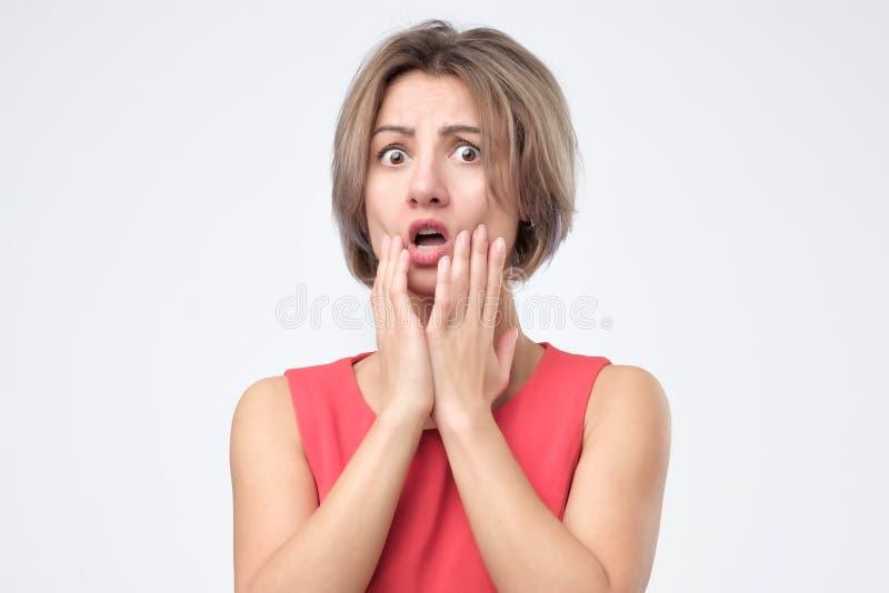 Förvånad chockad kvinnlig som bär röd klänning r och att hålla hennes hand på kind, öppnande mun arkivbild