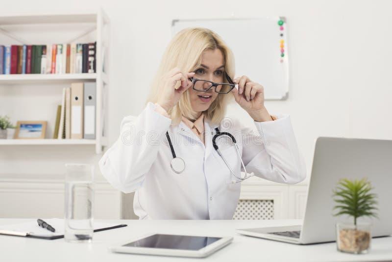 Förvånad doktor med exponeringsglas som sitter på skrivbordet royaltyfri foto