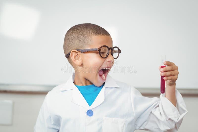Förvånad elev med labblaget som ser provröret arkivfoto
