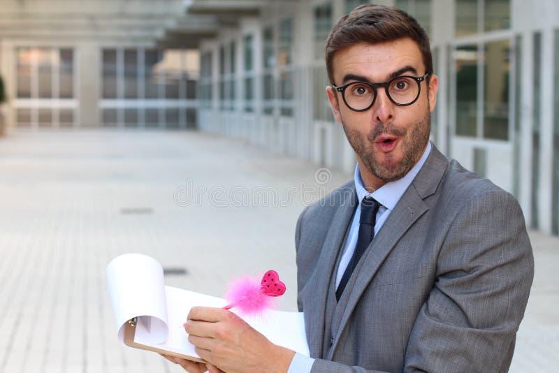 Förvånad flamboyant affärsman som tar anmärkningar med en gullig rosa färgpenna royaltyfri foto