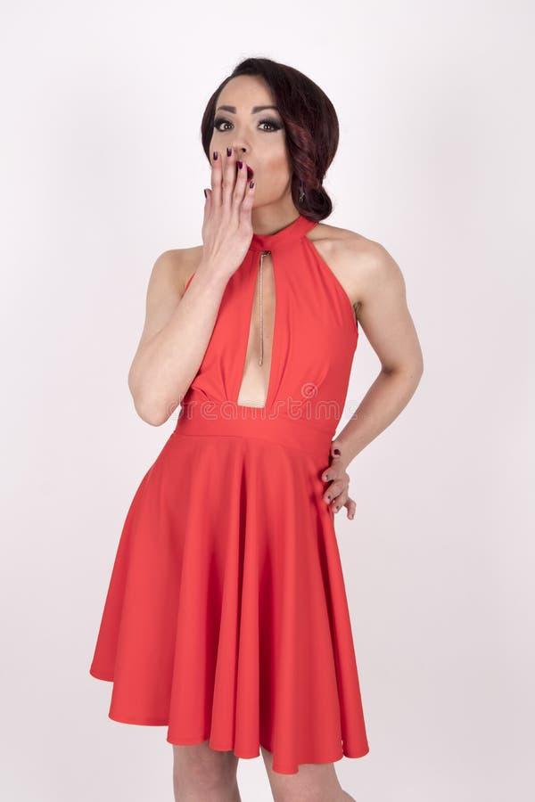 Förvånad flicka i en röd klänning med höga häl royaltyfri foto