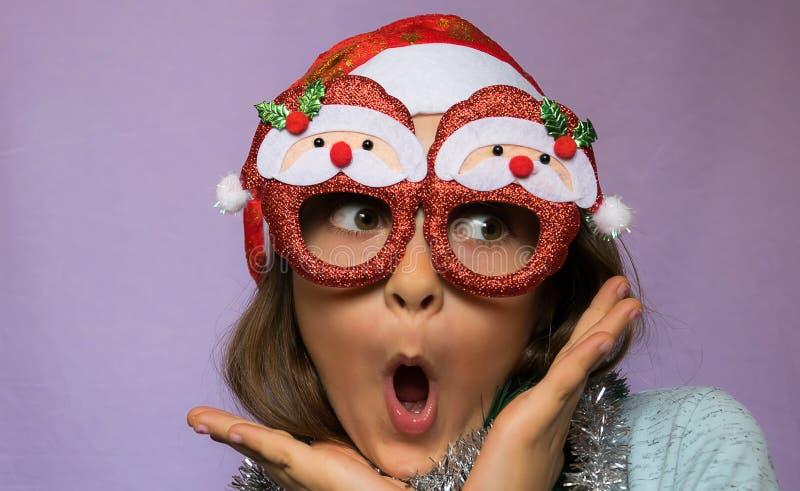 Förvånad flicka i hatt och exponeringsglas för jultomten s royaltyfri fotografi