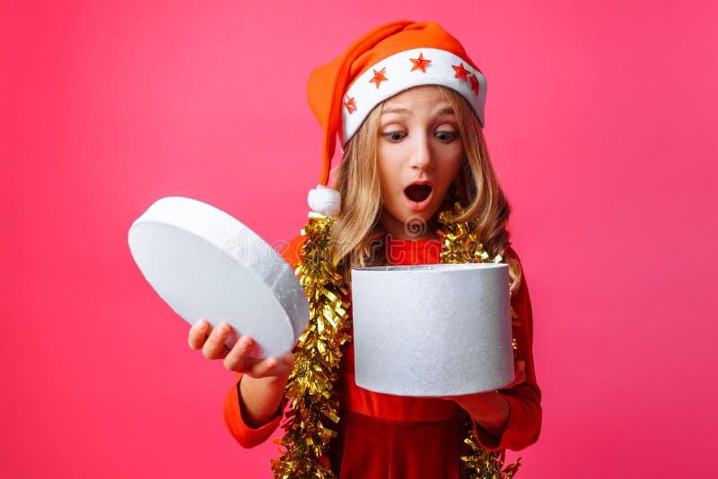 Förvånad flicka i jultomtenhatt och med glitter runt om hennes tonåriga hals fotografering för bildbyråer