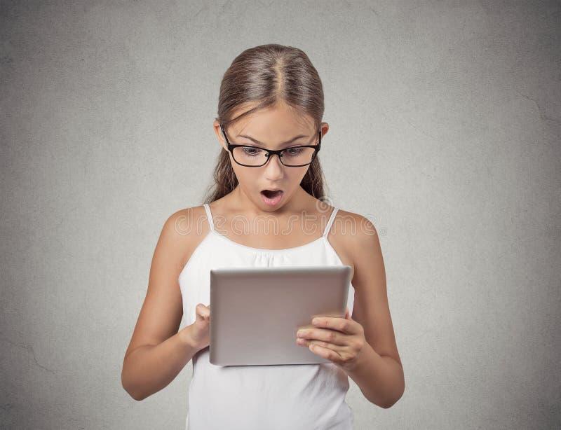 Förvånad flicka med exponeringsglas genom att använda blockdatoren arkivbild