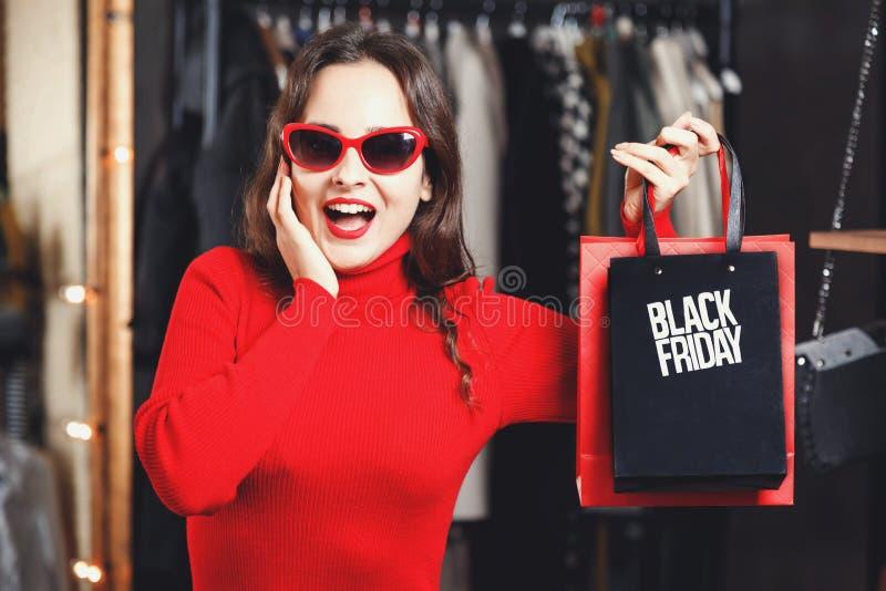 Förvånad flicka som visar den Black Friday påsen royaltyfria foton