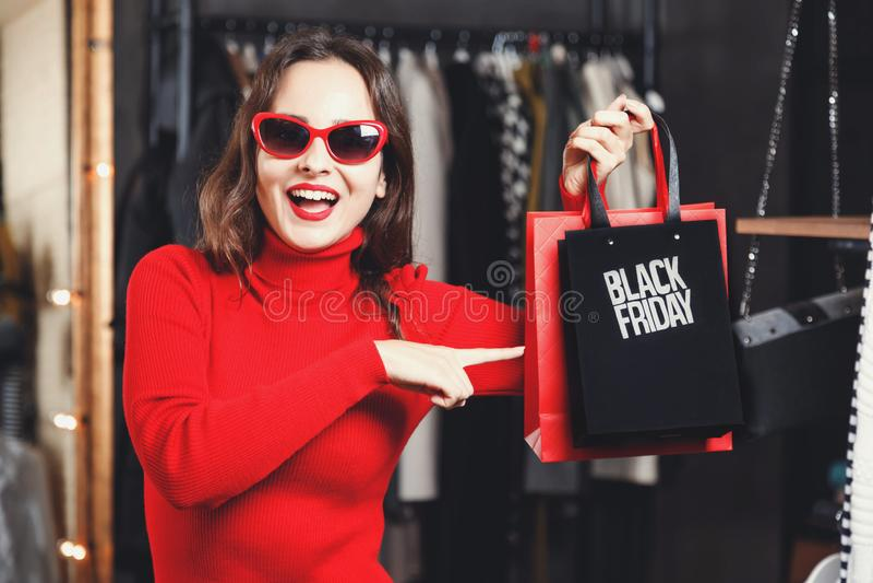 Förvånad flicka som visar den Black Friday påsen arkivbilder