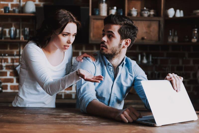 Förvånad fru som spionerar på make med bärbara datorn arkivfoto