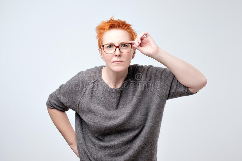 Förvånad frustrerad mogen kvinna med rött hår Hon har problem med synförmåga arkivfoton