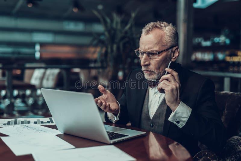 Förvånad gammal affärsman som ser bärbara datorn arkivbild