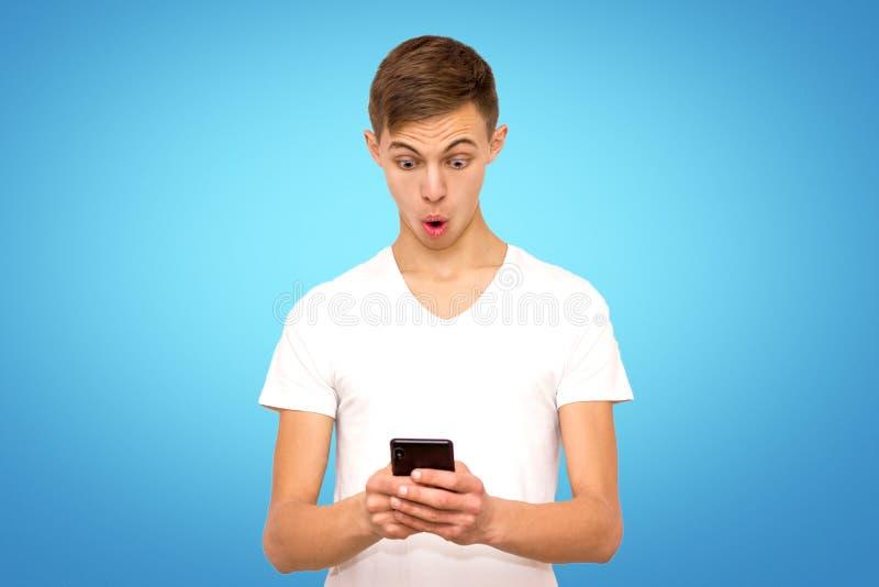 Förvånad grabb i den vita t-skjortan med telefonen, isolat, man på blå bakgrund royaltyfria foton