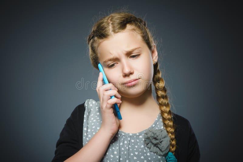 Förvånad gullig flicka med mobiltelefonen Isolerat på grå färg royaltyfri foto