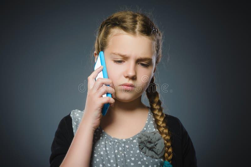 Förvånad gullig flicka med mobiltelefonen Isolerat på grå färg royaltyfri fotografi