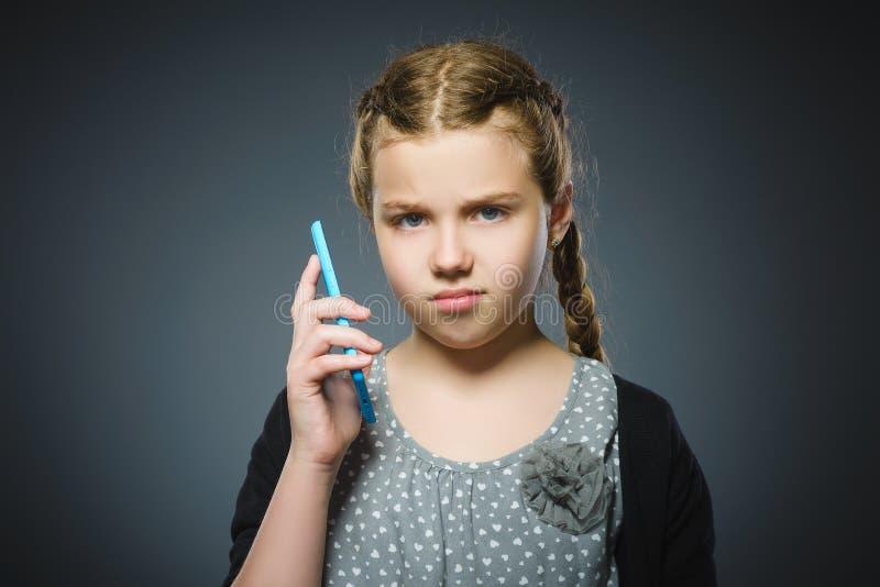 Förvånad gullig flicka med mobiltelefonen Isolerat på grå färg arkivbild