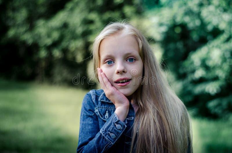 Förvånad gullig liten blond flicka på sommarfältet royaltyfria bilder
