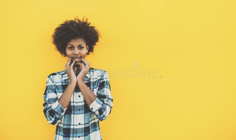 Förvånad gullig svart lockig flicka royaltyfri bild