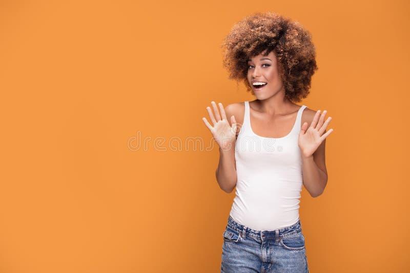 Förvånad häpen härlig afro kvinna med öppen le mou för sned boll royaltyfri foto