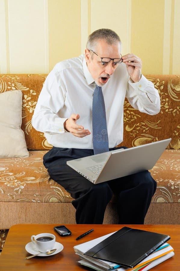 Förvånad hög affärsman med datoren royaltyfria foton