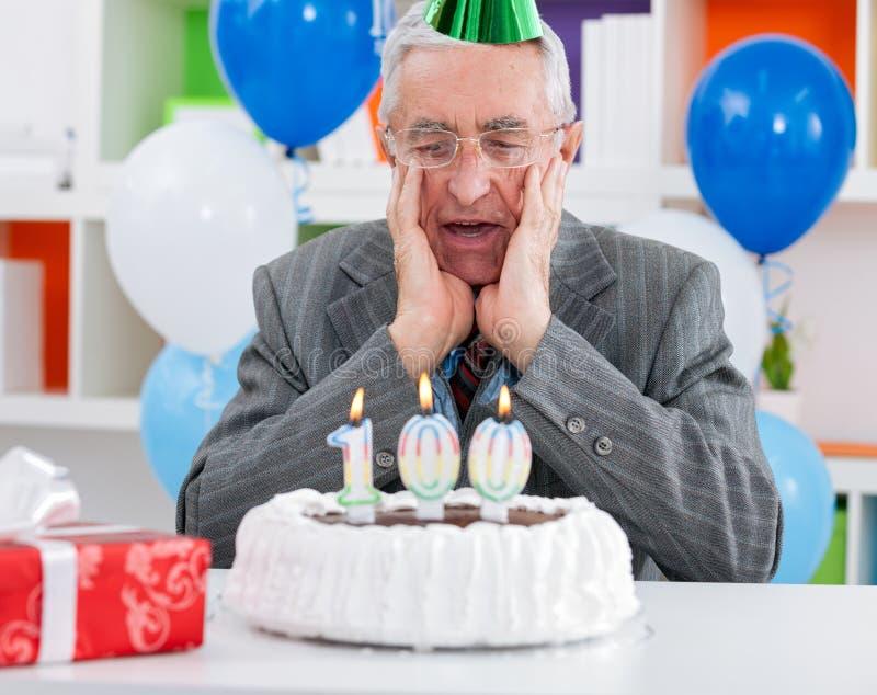 Förvånad hög man som ser födelsedagkakan arkivfoton