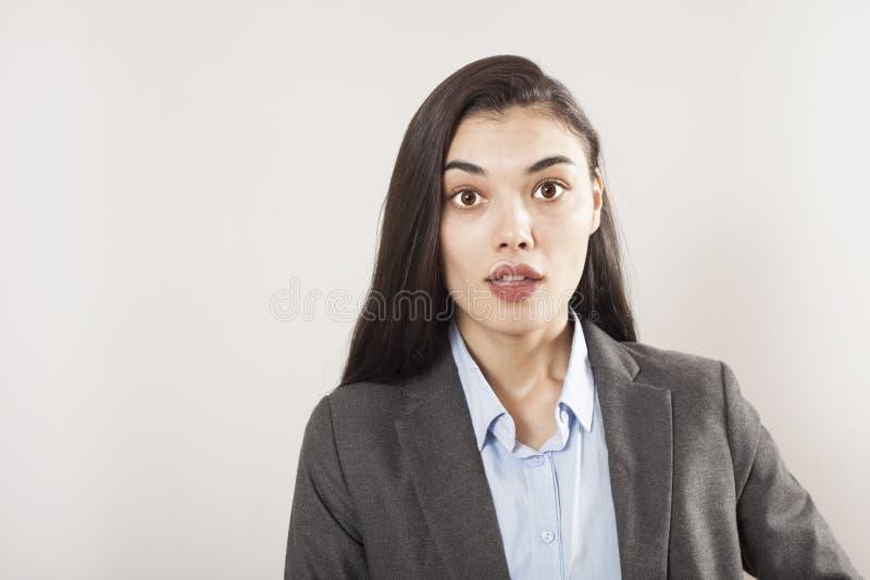 Förvånad kvinna för överraskning Closeupståendekvinna som ser förvånad oavkortad isolerad grå väggbackgroun för misstro bred öppe royaltyfria bilder
