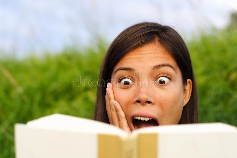 förvånad kvinna för bokavläsning arkivbild