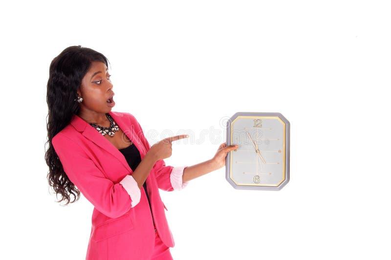 förvånad kvinna för klockaholding arkivbild
