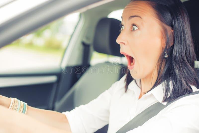 Förvånad kvinna i bilen royaltyfria foton