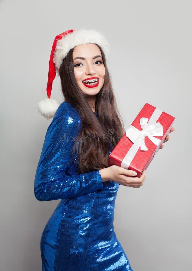 Förvånad kvinna i hänglsen som rymmer julgåvan Flicka i försäljningsbegrepp för jultomten hatt, för Xmas eller för nytt år arkivfoton