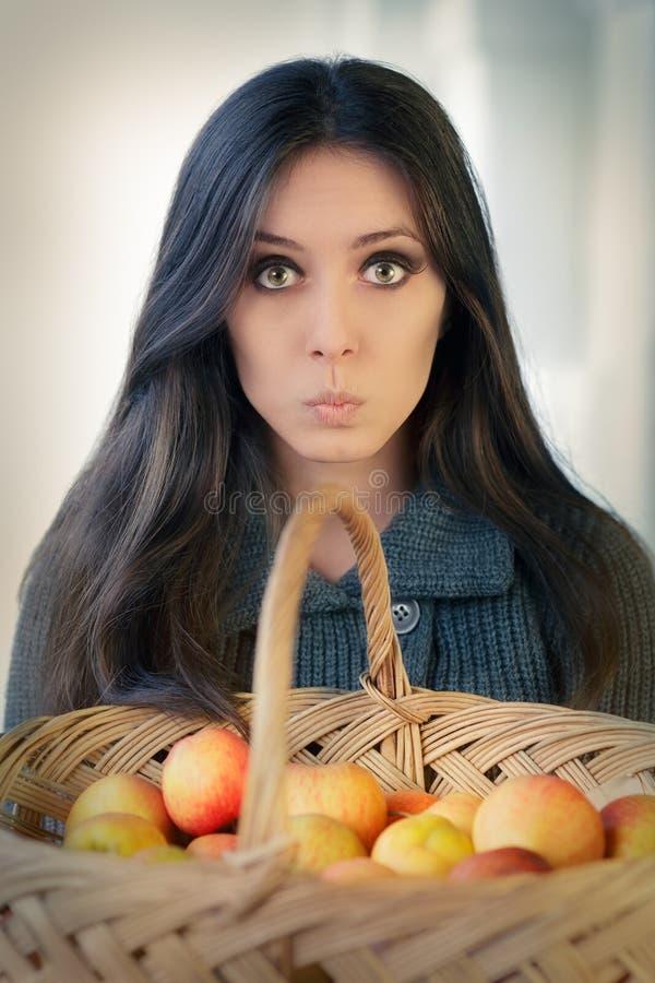 Förvånad kvinna med en korg av mogna äpplen arkivbilder