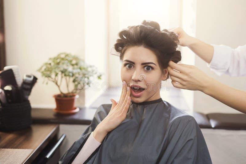 Förvånad kvinna med hårrullar på huvudet i hårsalong royaltyfri bild
